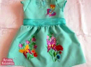 Błękitka sukienka dla dziecka, na której wyhaftowane zostały kwiaty i kolorowe motyle - całość wykonana przez twórczynię Mariannę Madanowską