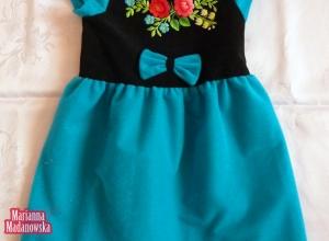 Błękitna sukienka dla dziewczynki wyhaftowana ręcznie przez Mariannę Madanowską łowickimi motywami folklorystycznymi