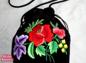 Czerwone róże, zółte konwalie i inne kwiaty wyhaftowane ręcznie na łowickiej sakiewce z czarnego aksamitu