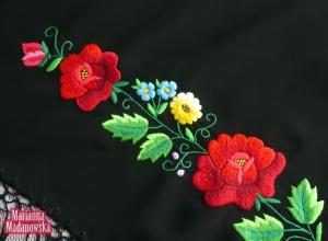 Część haftu ręcznego z czerwonymi różami wykonanego na chuście łowickiej jako przykład folkloru łowickiego