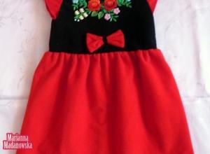 Dziewczęca czerwona sukienka z kokardą wyhaftowana motywami ludowymi po łowicku