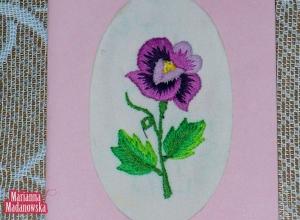 Fioletowa pocztówka zdobiona wyhaftowanym ręcznie fioletowym kwiatem autorstwa Marianny Madanowskiej