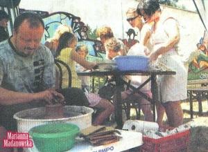 Jacek Tratkiewicz toczy dzbanek na kole garncarskim, w tle - maluchy pracujące nad glinianymi miskami.