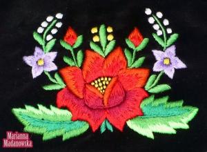 Kolorowy folklor łowicki przedstawiony poprzez ręcznie wyhaftowane kwiaty na sakiewce damskiej