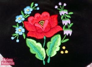 Łowickie konwalie, niezapominajki i róża wyhaftowane na sakiewce jako element łowickiego folkloru