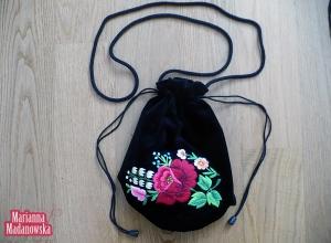 Piękna czerwona róża w otoczeniu innych kwiatów na haftowanym ręcznie woreczku