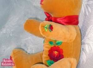 Pomarańczowy pluszowy miś ozdobiony ręcznie wyhaftowanymi czerwonymi różami - twórczość Marianny Madanowskiej