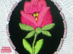 Ręcznie haftowana różowa różyczka na wisiorku łowickim autorstwa Marianny Madanowskiej