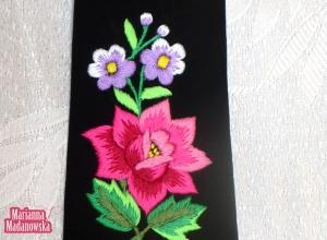 Różowa róża i fioletowe niezapominajki na krawacie łowickim jako przejaw łowickiego folkloru w hafcie