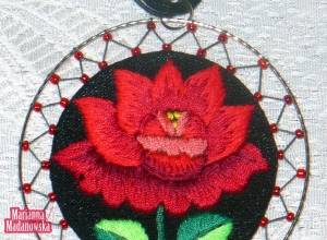 Soczysta czerwona róża wyhaftowana na ręcznie zrobionym łowickim naszyjniku
