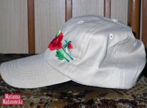 Widok z boku na szarą czapkę z daszkiem wyszywaną ręcznym haftem łowickim przez Mariannę Madanowską