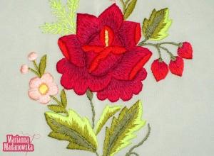 Wyrazisty motyw czerwonej róży w połączeniu z niezapominajkami wyhaftowany ręcznie na pastelowo-zielonej chuście łowickiej