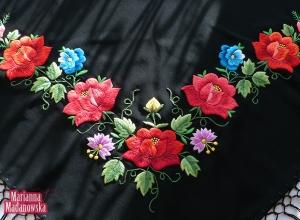 Zbliżenie na łowicki wzór kwiatowy wyhaftowany ręcznie na czarnej chuście