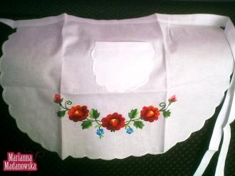 Fartuszek zdobiony przez Mariannę Madanowską ręcznie haftowanymi łowickimi różami i niezapominajkami
