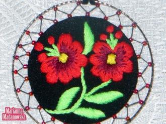 Zbliżenie na ręcznie haftowany przez Mariannę Madanowską wisiorek łowicki